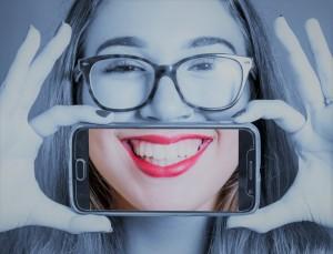 ragazza con smartphone che si scatta una foto al proprio sorriso